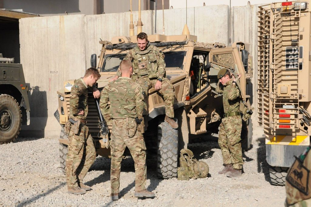 four reserves chat while standing around an army vehicle against a Kabul backdrop.