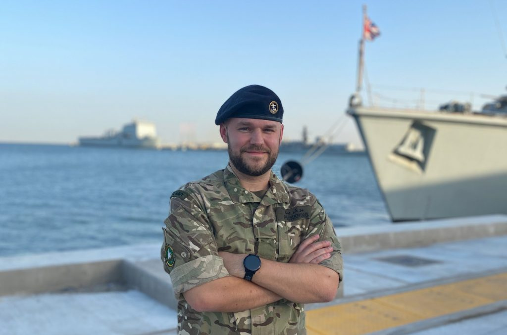 Naval reserve standing beside big ship in a sunny setting