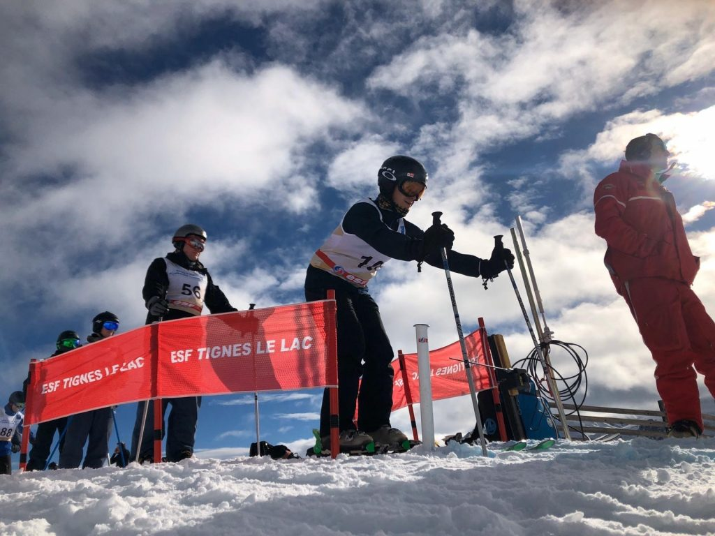 Skiers getting ready to descend a snowy mountain