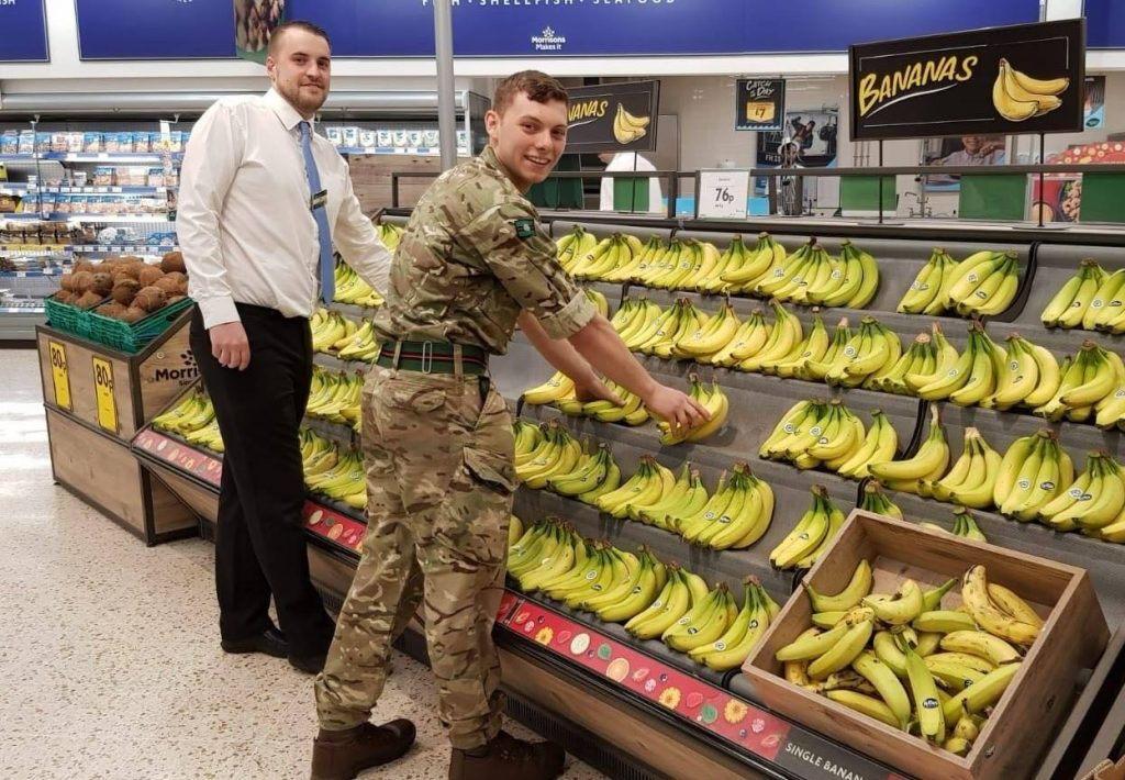 Reservist in uniform stacking bananas at Morrisons.