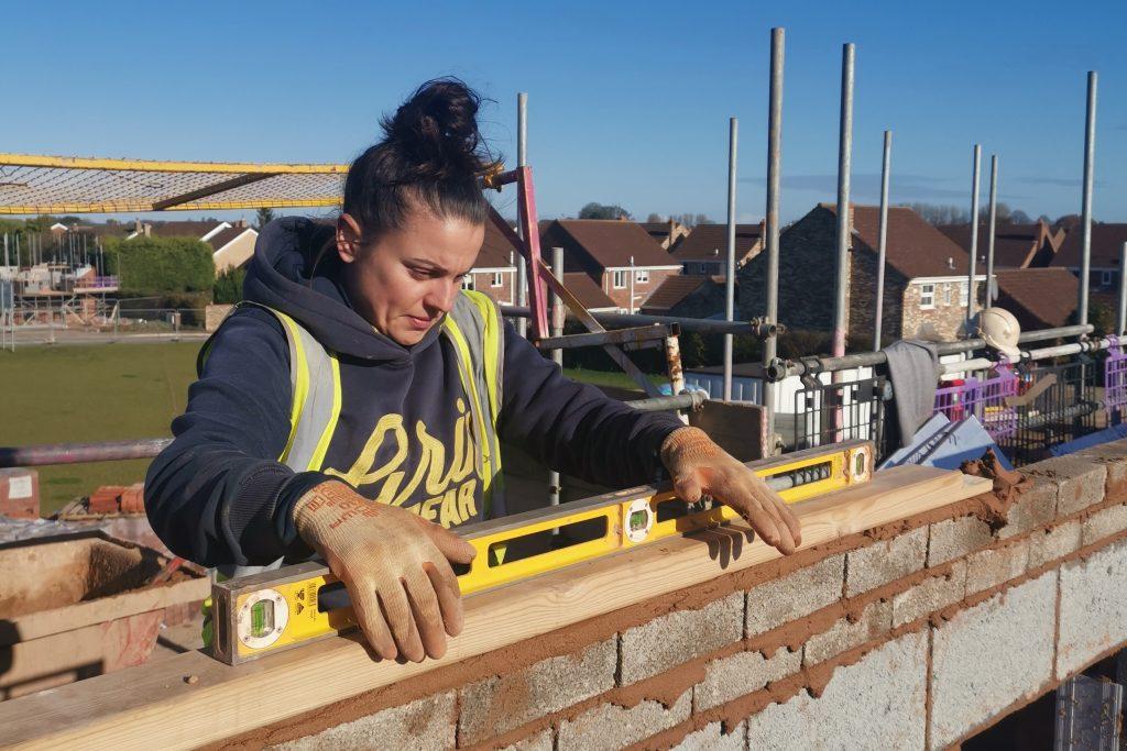 Woman in hi vis waistcoat laying bricks