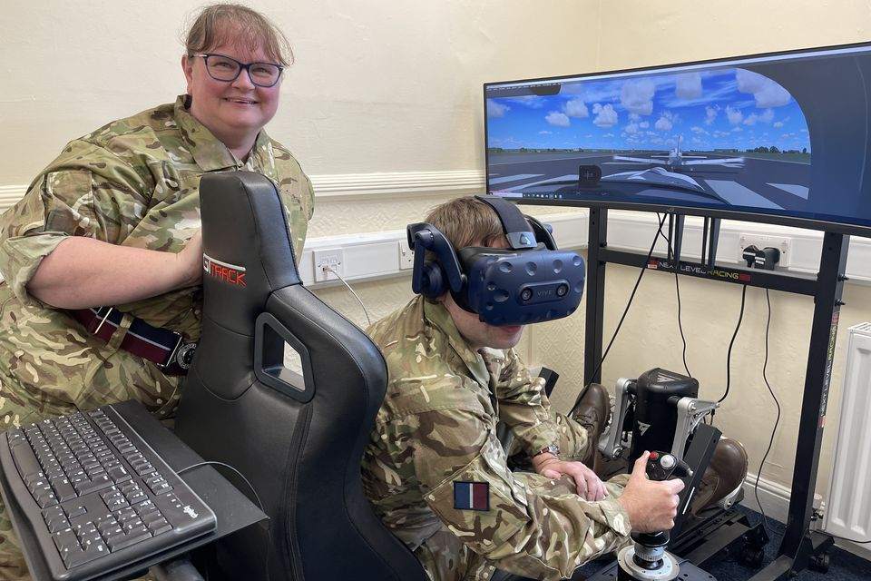 Woman adult volunteer oversees another volunteer at the controls of the virtual reality aircraft simulator