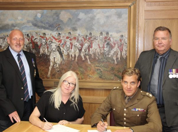Three executives from Clipper Group signing Armed Forces Covenant with soldier Julian Salusbury.