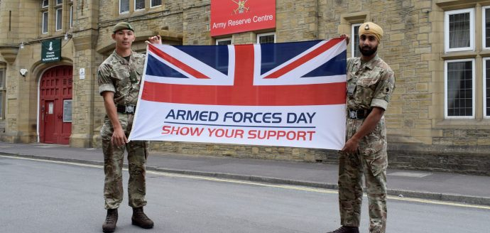 Two reserves from 4YORKS carry the Armed Forces Week flag