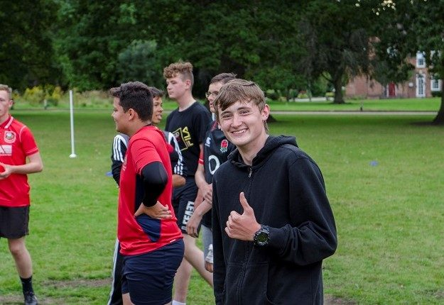 Smiling cadet playing football on camp
