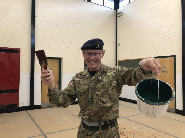 Cadet volunteer with paint brush and can