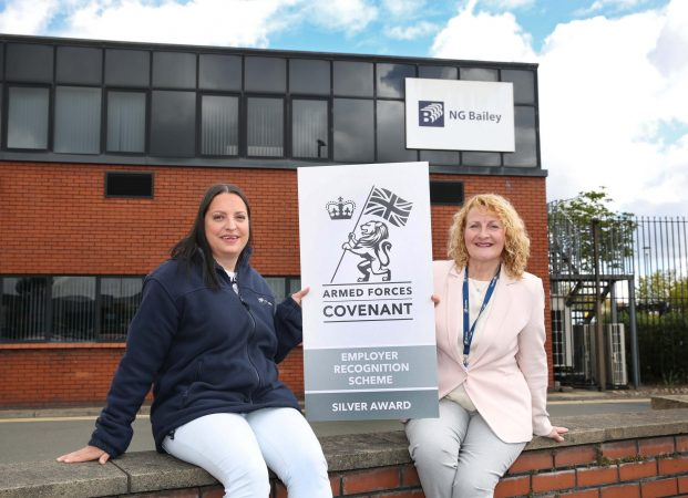 Two women holding a Silver Award banner outside the office of NG Bailey