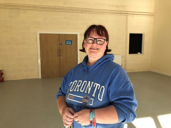 Smiling adult volunteer in empty drill hall