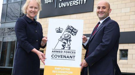 Woman and man holding a Gold Award banner outside York St John University