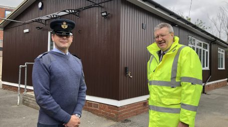 Air Cadet adult volunteer with man in high visibility jacket outside hut
