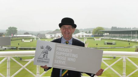 Man in bowler hat holds Armed Forces Covenant Sign