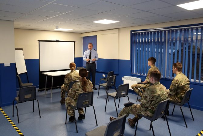 Cadets in classroom in front of white board with volunteer addressing them