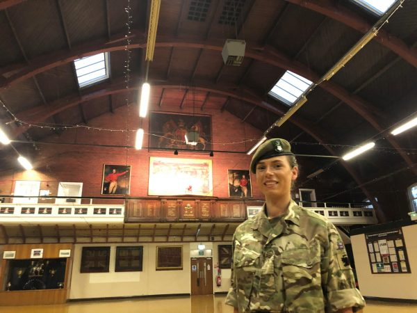 female reserve soldier in the middle of a drill hall with vast, arching roof