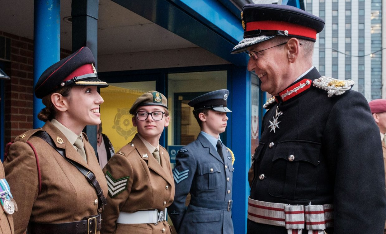 Female reserve smiling at Lord Lieutenant during ceremonial line-up