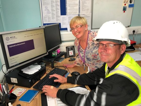 Man in hard hat in front of computer with smiling woman