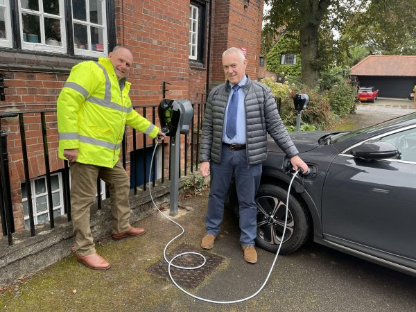 Man in yellow jacket and another man by vehicle charging point