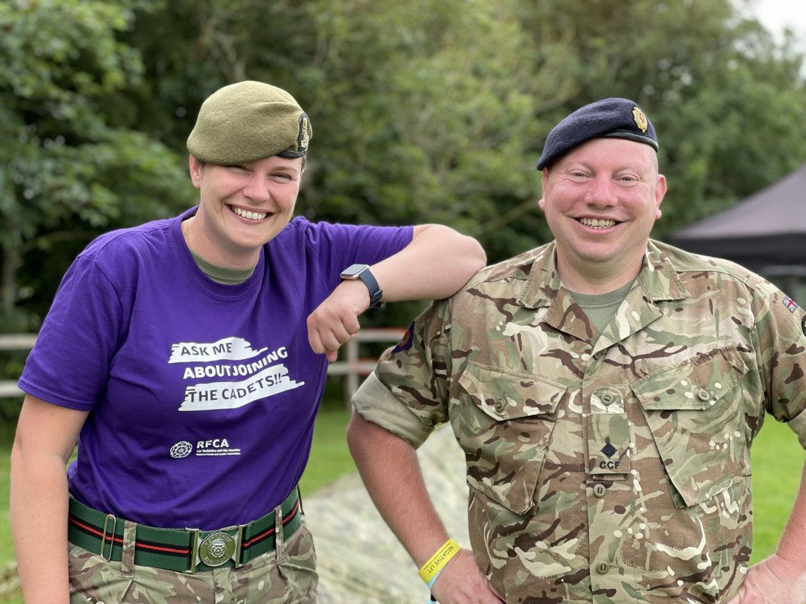 Two cadet force adult volunteers , one wearing a bright purple t-shirt promoting the cadets